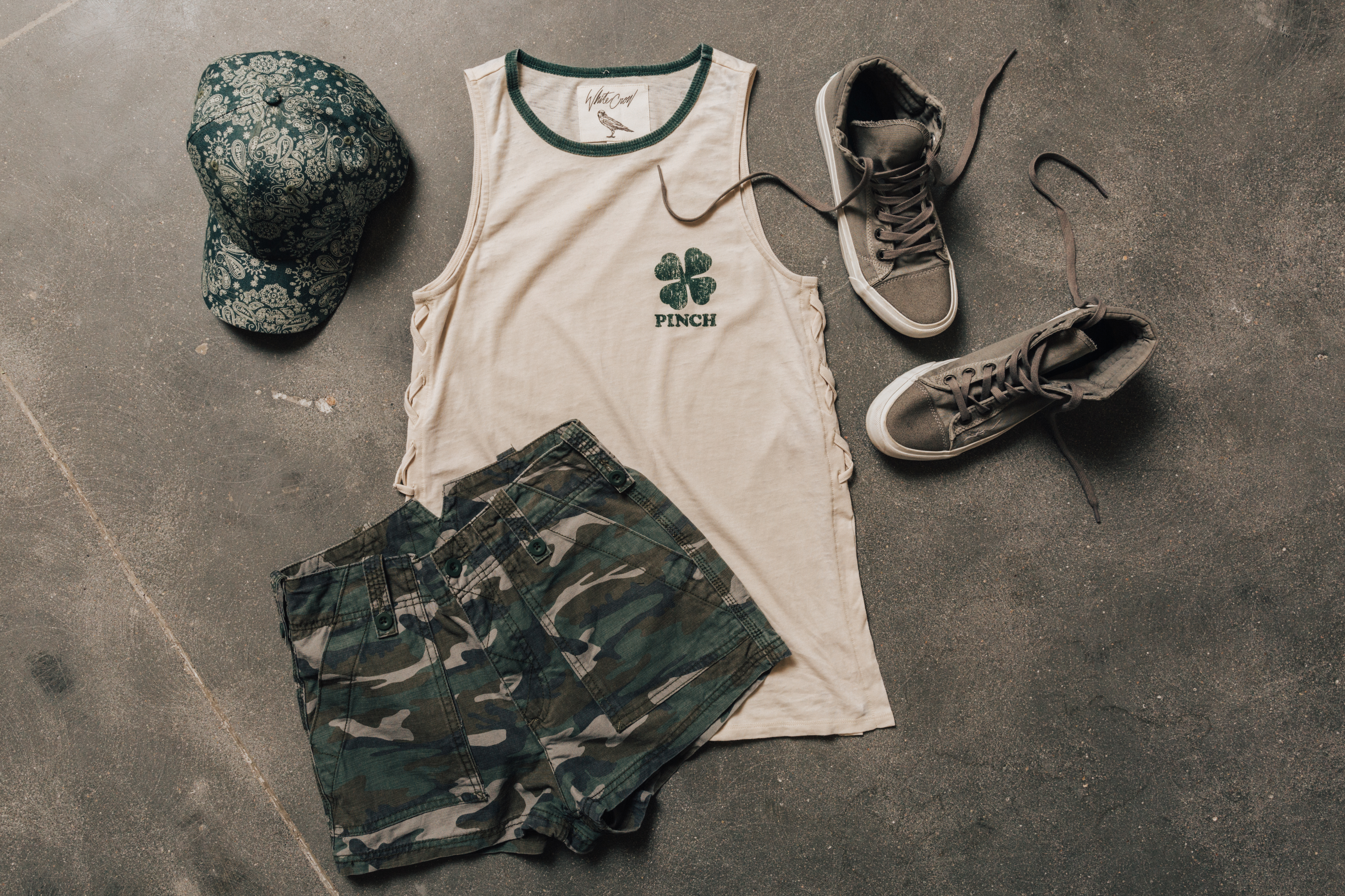 St. Patrick's Day lay down with white and green piped Pinch t-shirt with shamrock detail, camo print Free People shorts, paired with tennis shoes and a green hat.