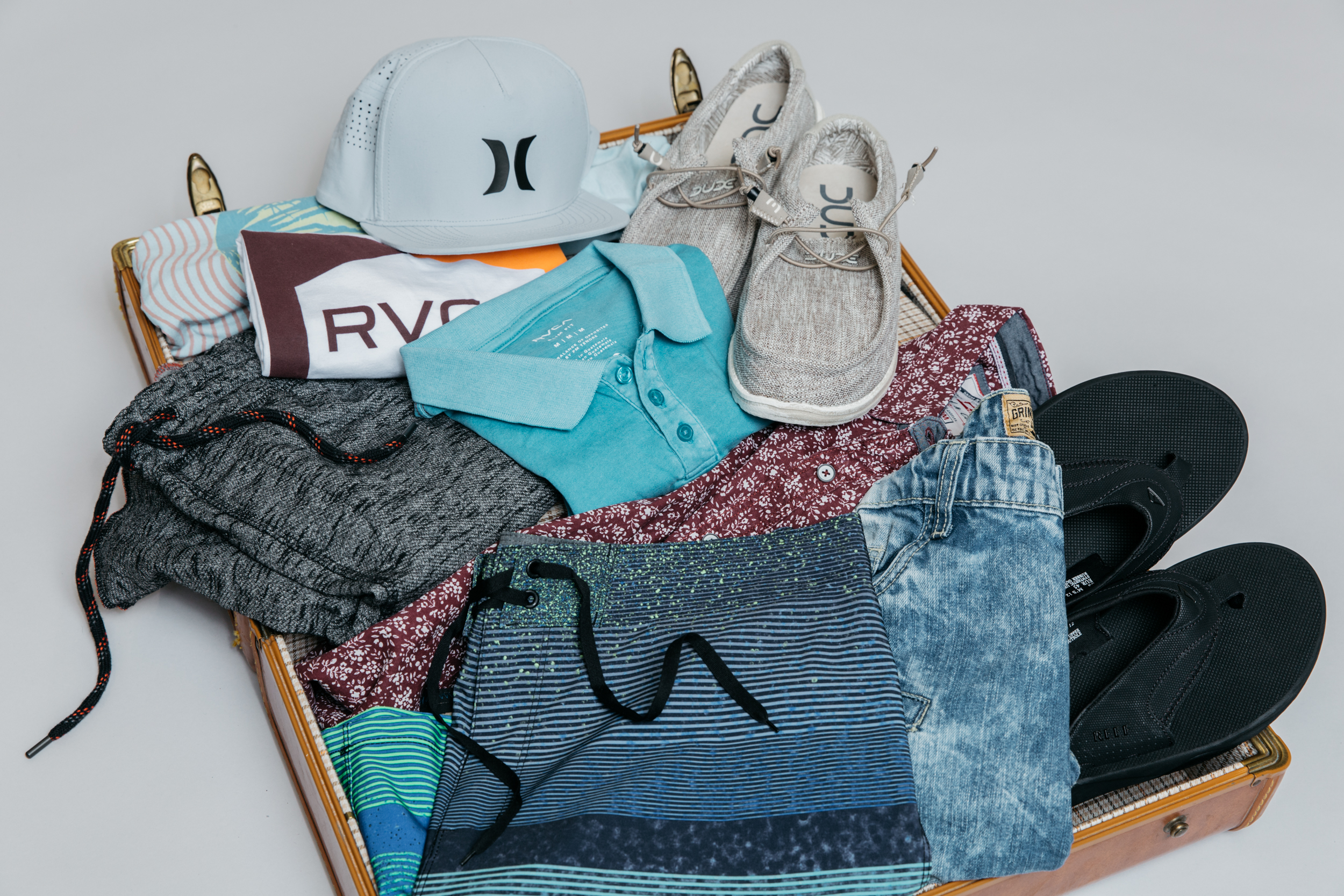 Vintage suitcase packed, with men's clothing including Hurley boardshorts and a trucker hat, a RVCA tank top, and Hey Dude casual shoes, for a road trip with friends.