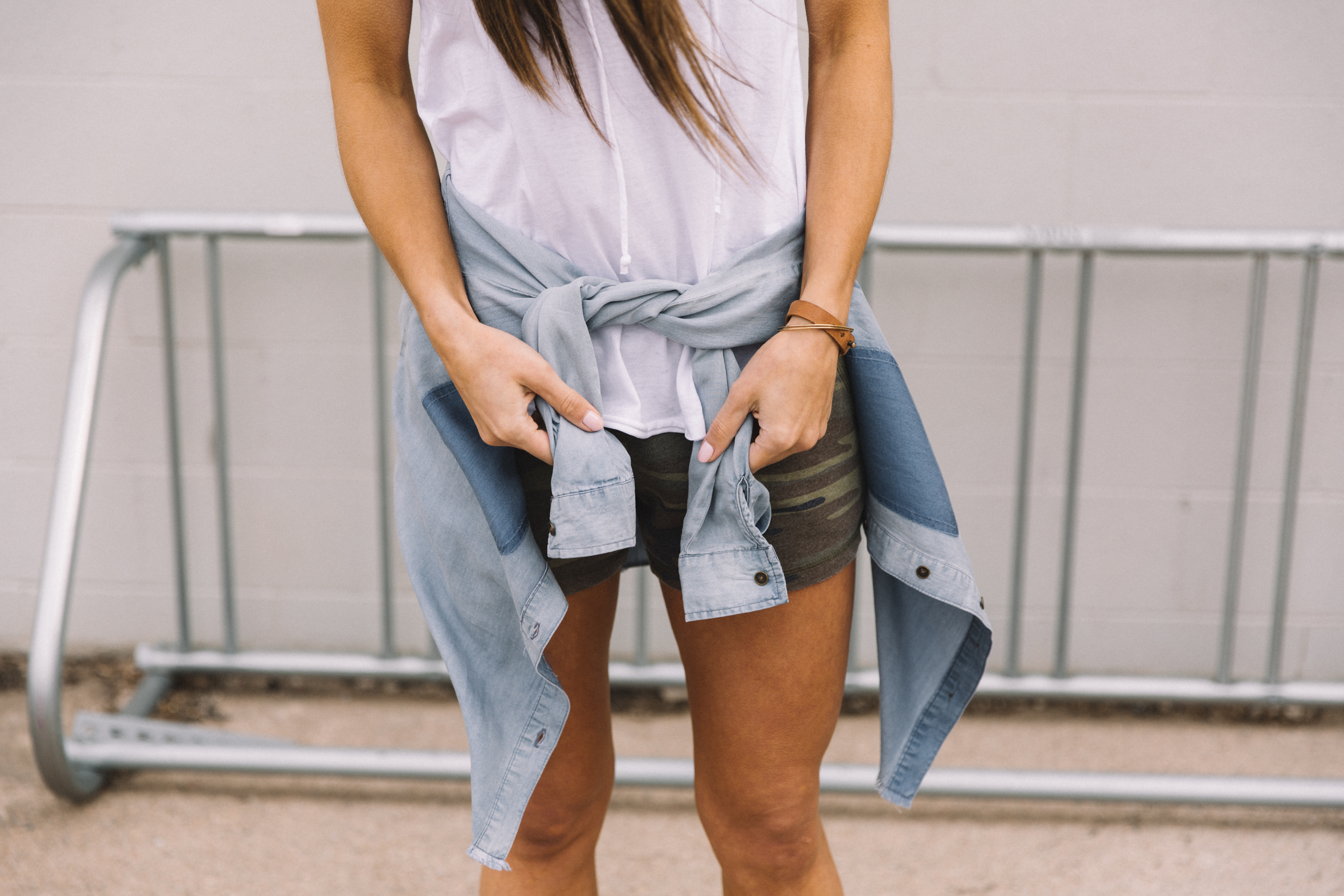 Women wearing a White Crow white lace-up tank top and french terry camo shorts, with a BKE chambray button-down top tied around her waist.