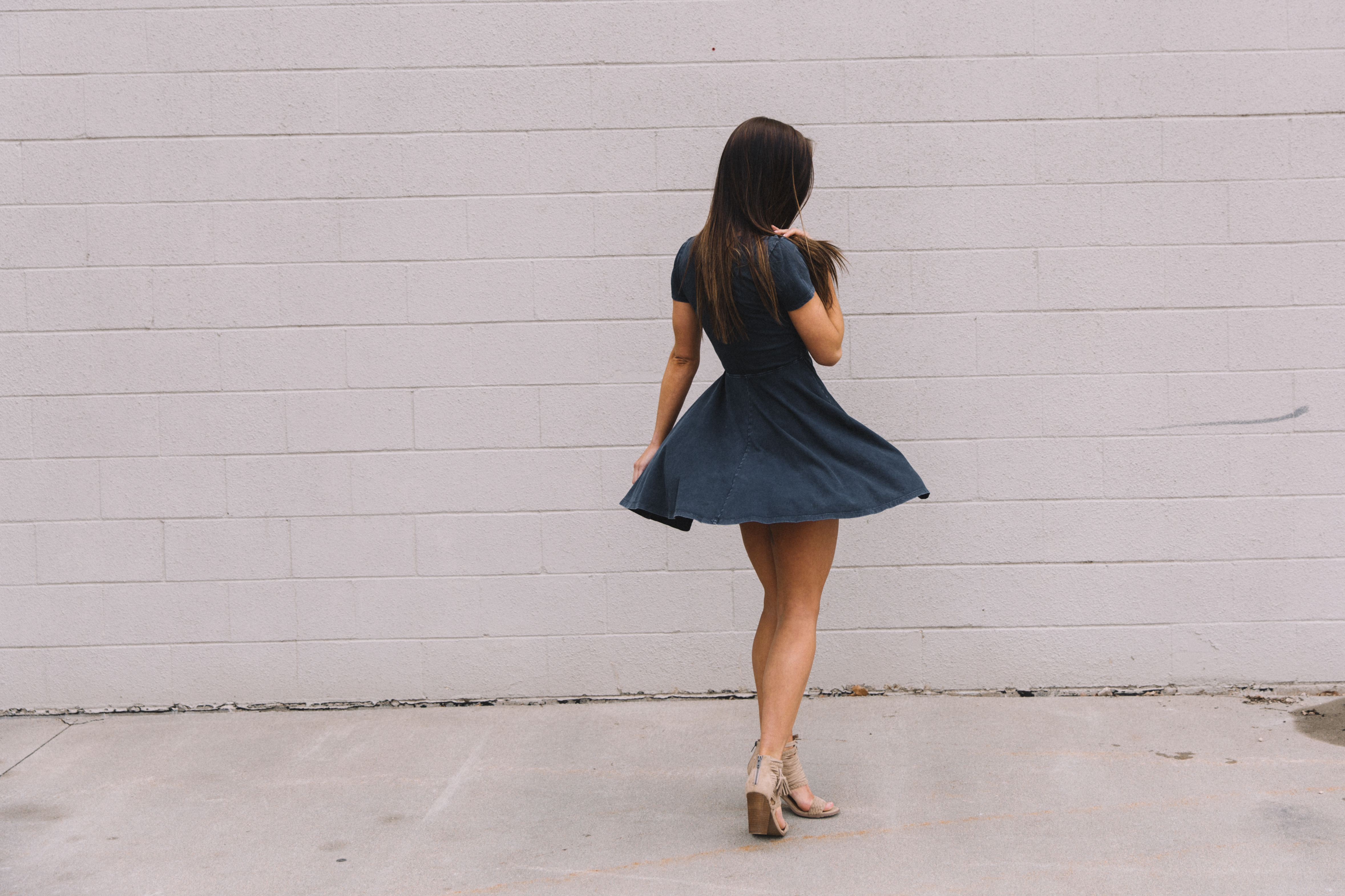 Women twirling while wearing a White Crow navy front-tie dress and Not Rated brand spring heels from the store Buckle.