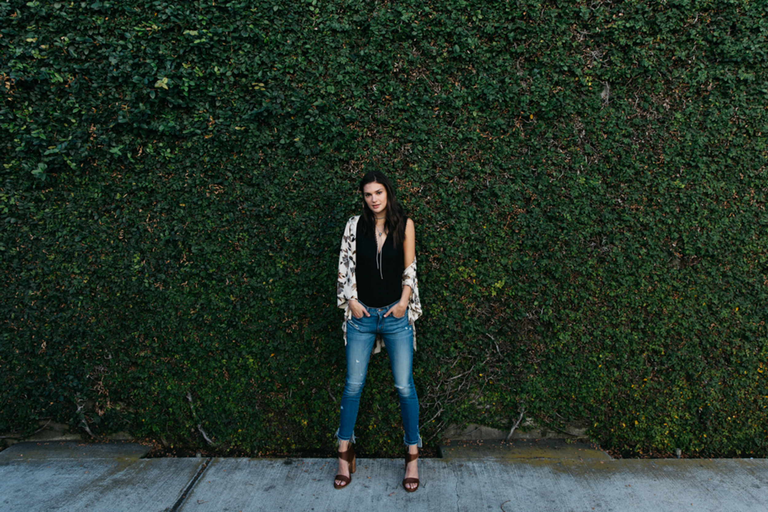 Woman standing against ivy-covered wall in raw-edge Flying Monkey jeans paired with a pair of cognac leather block heels and a floral kimono.