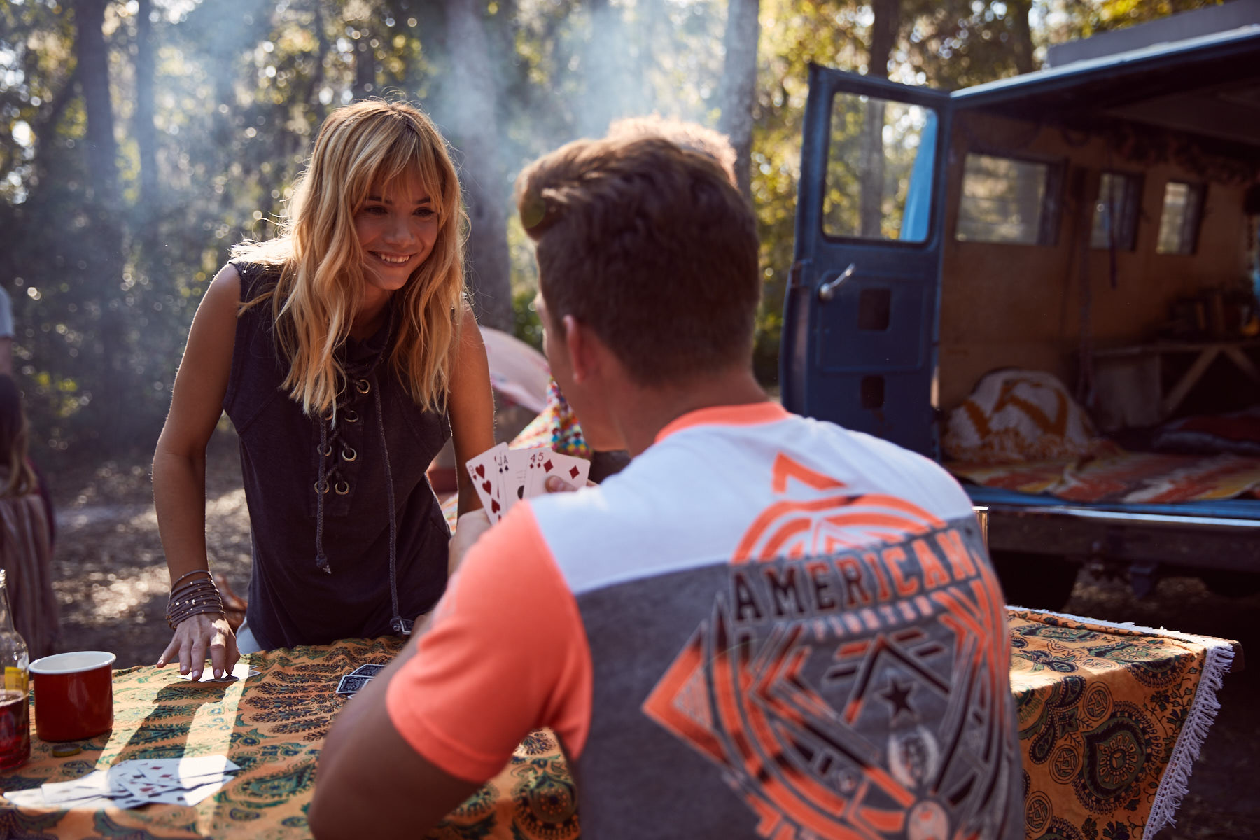 A young man and women, wearing Buckle clothing, playing cards with each other while on a friends camping trip.