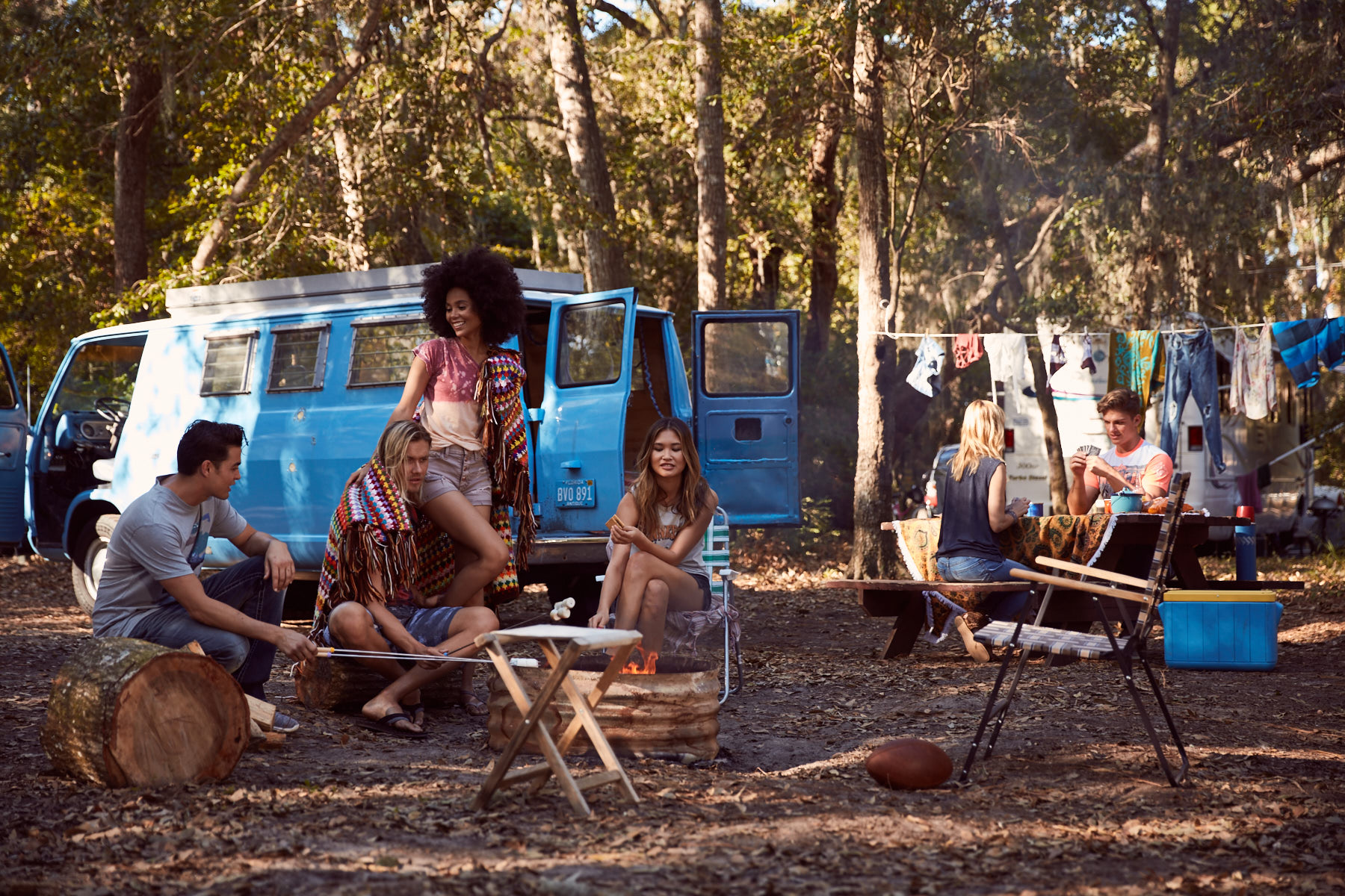 Group of six friends, wearing Buckle clothing, hanging out around the fire and playing cards, while on a camping trip.