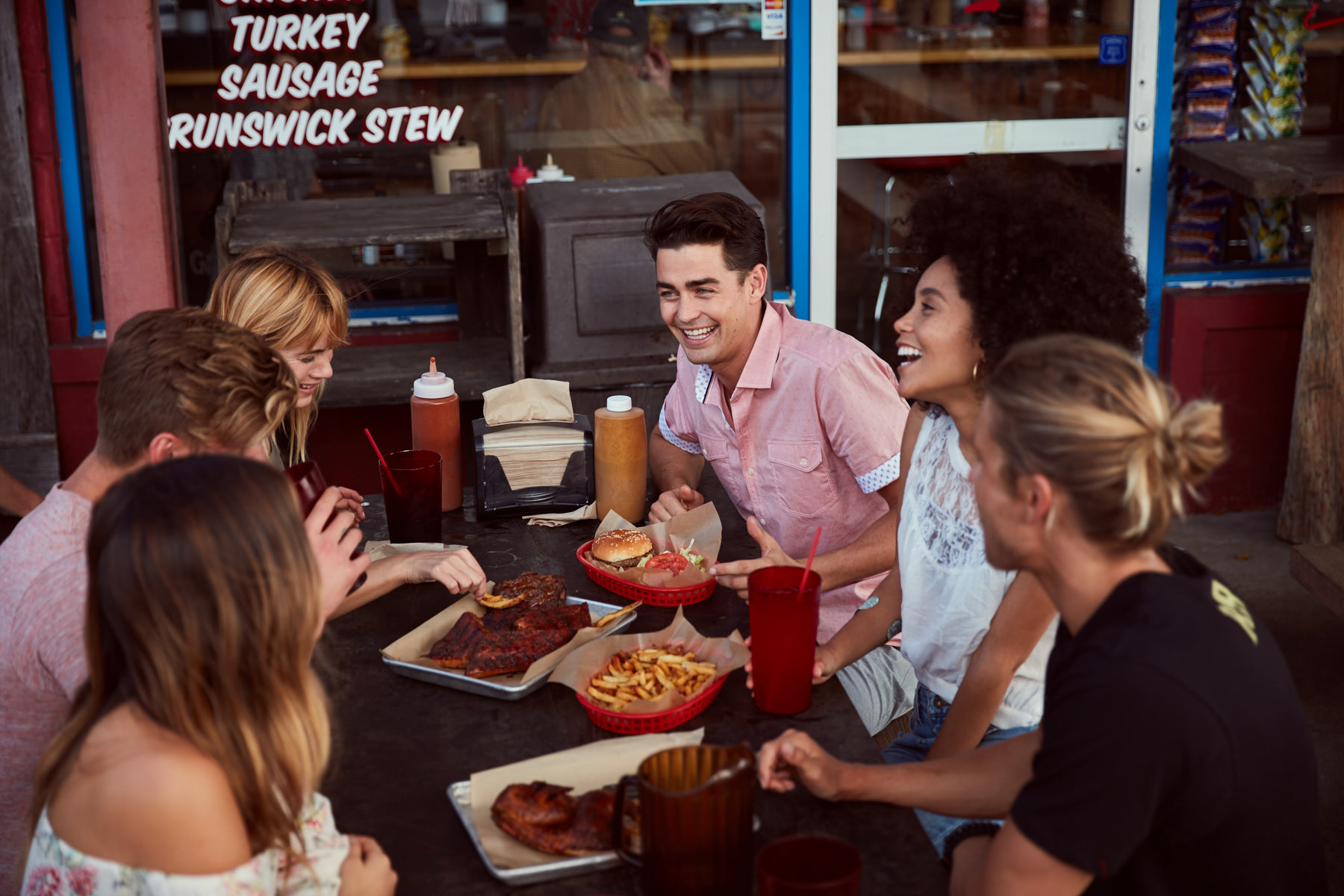 Group of six friends, wearing Buckle clothing, hanging out during a BBQ meal at a restaurant.