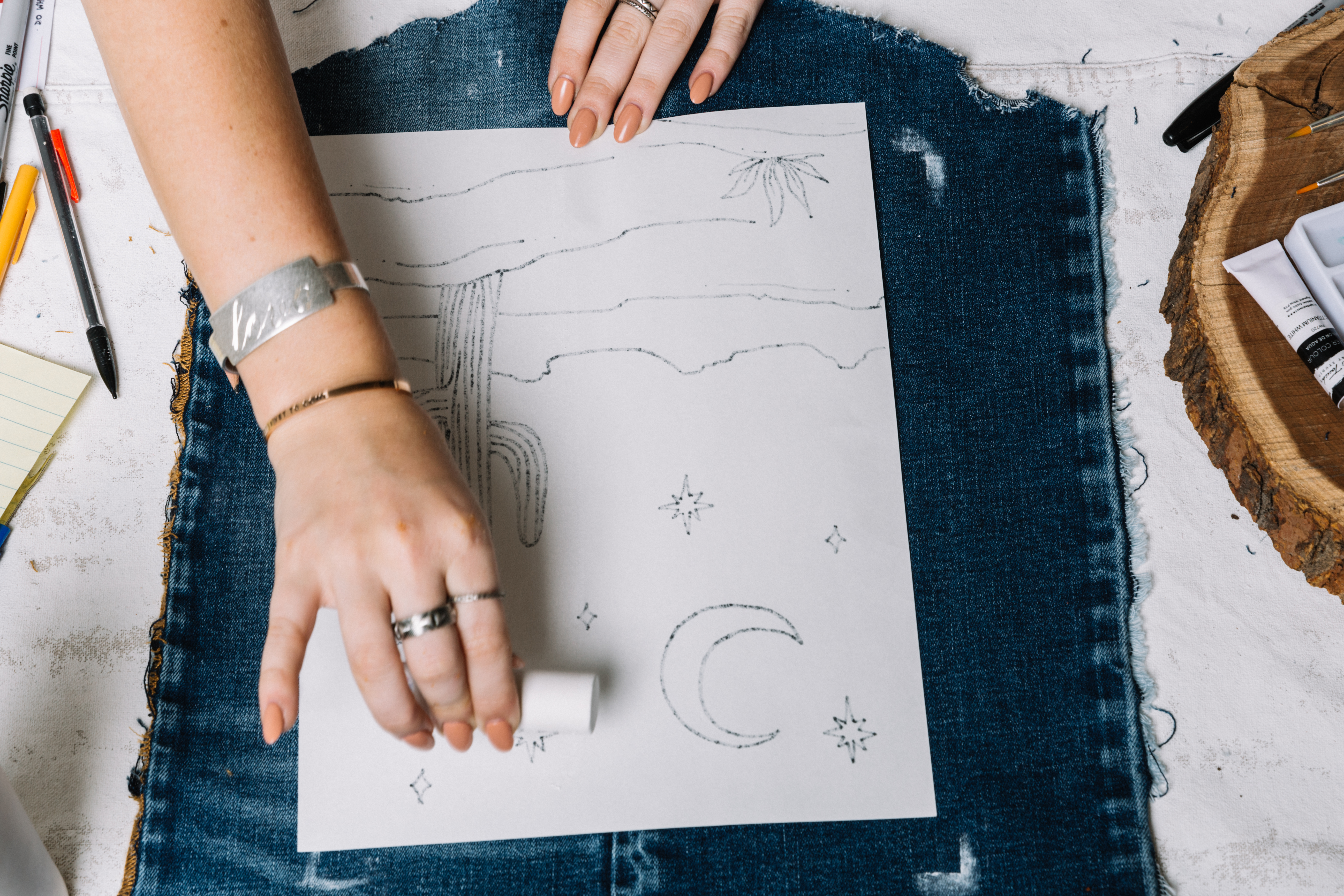 Tracing the design on a denim tapestry.
