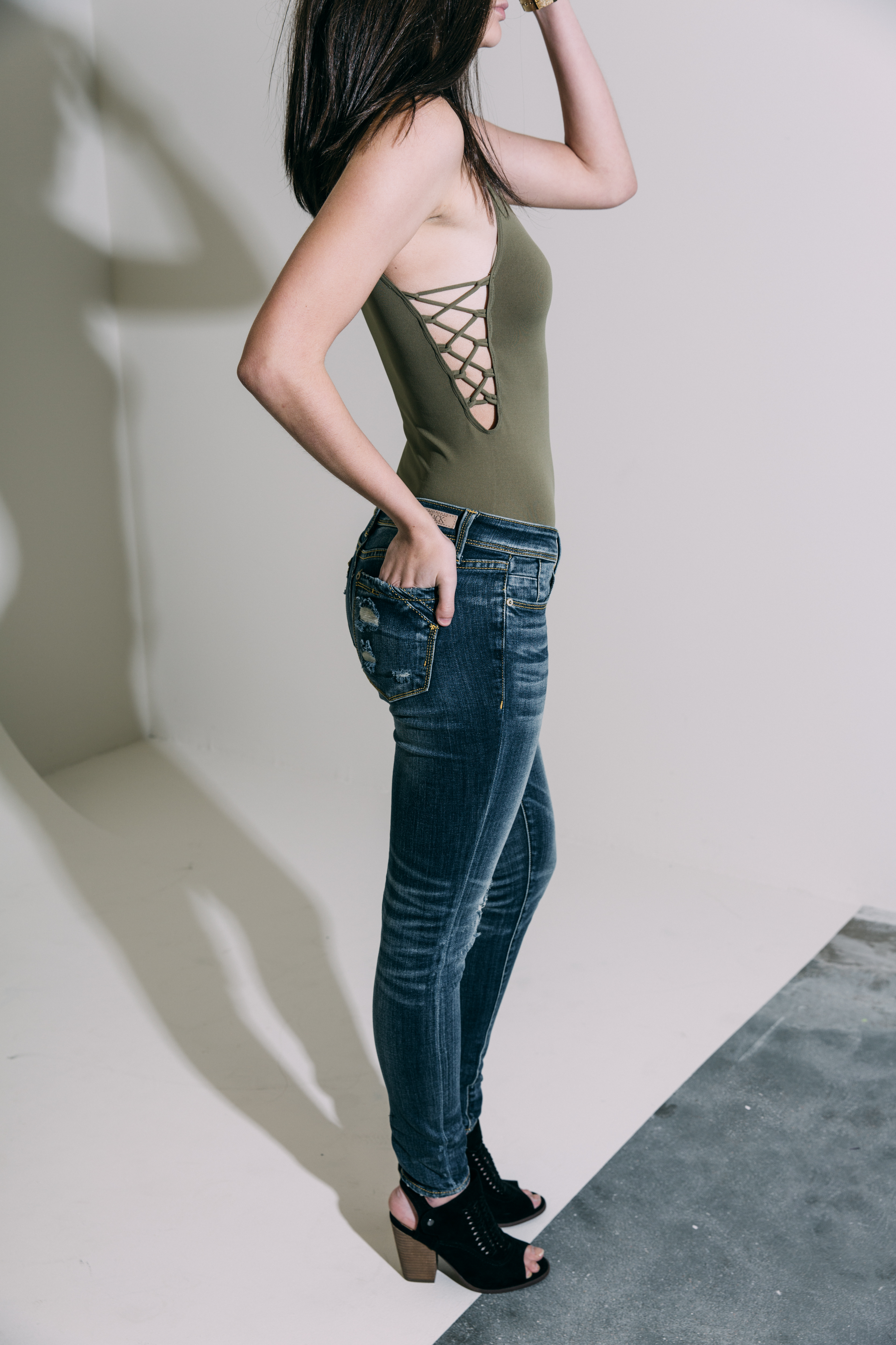 Ankle Skinny Buckle Black jeans on a girl in an olive Free People bodysuit.