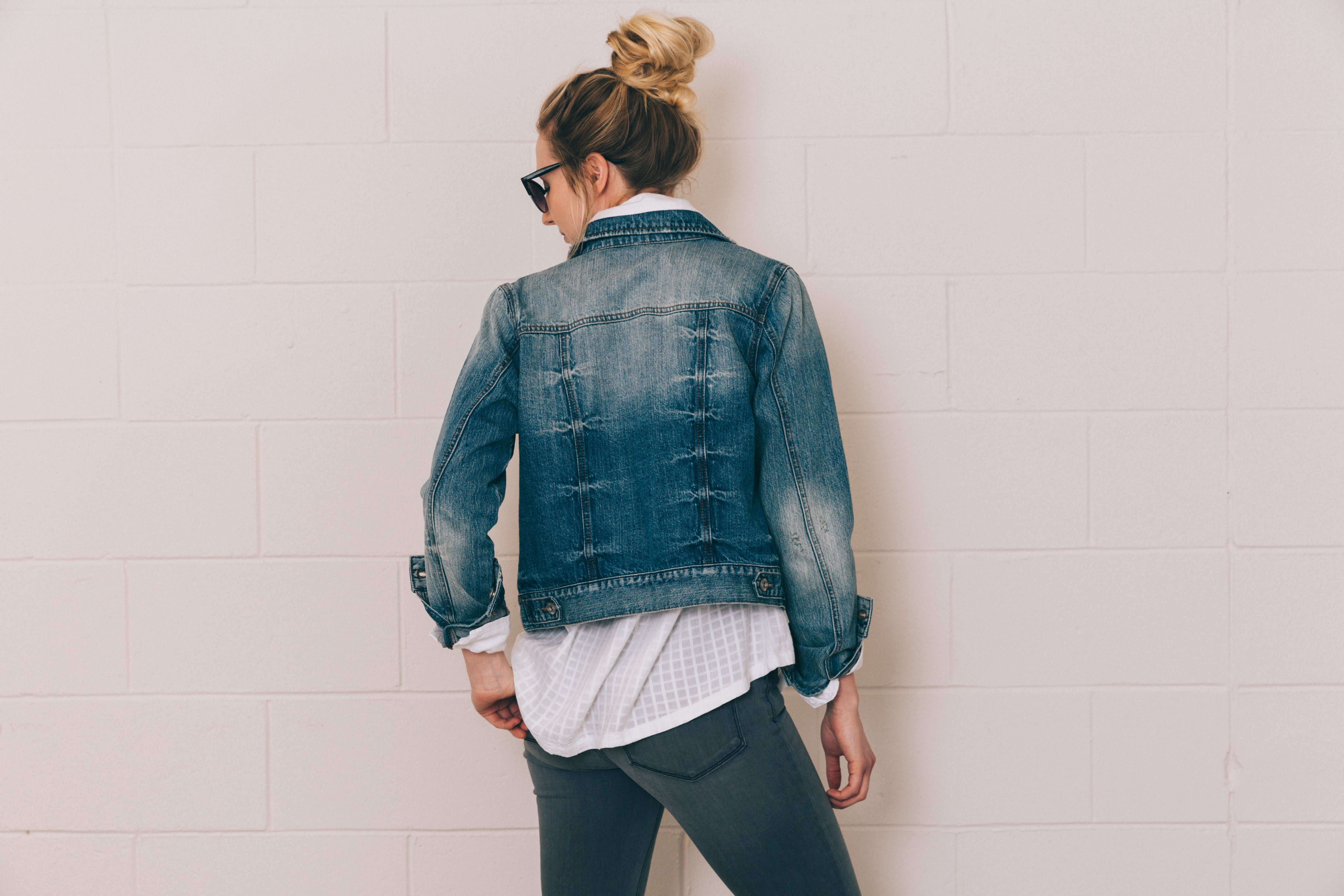 Girl in a white button-down, grey jeans, and a denim jacket.