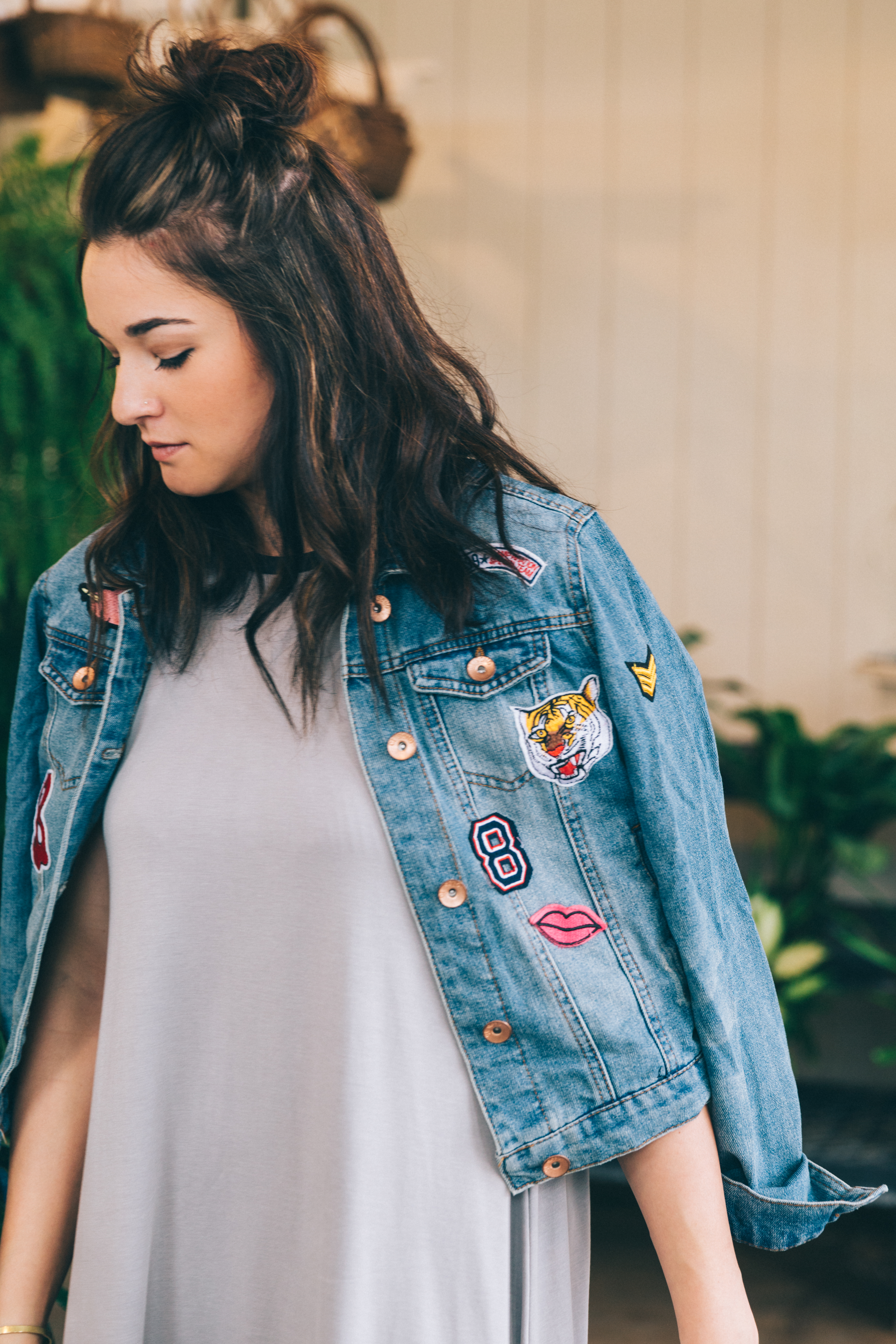 Girl in a dress and patch denim jacket.