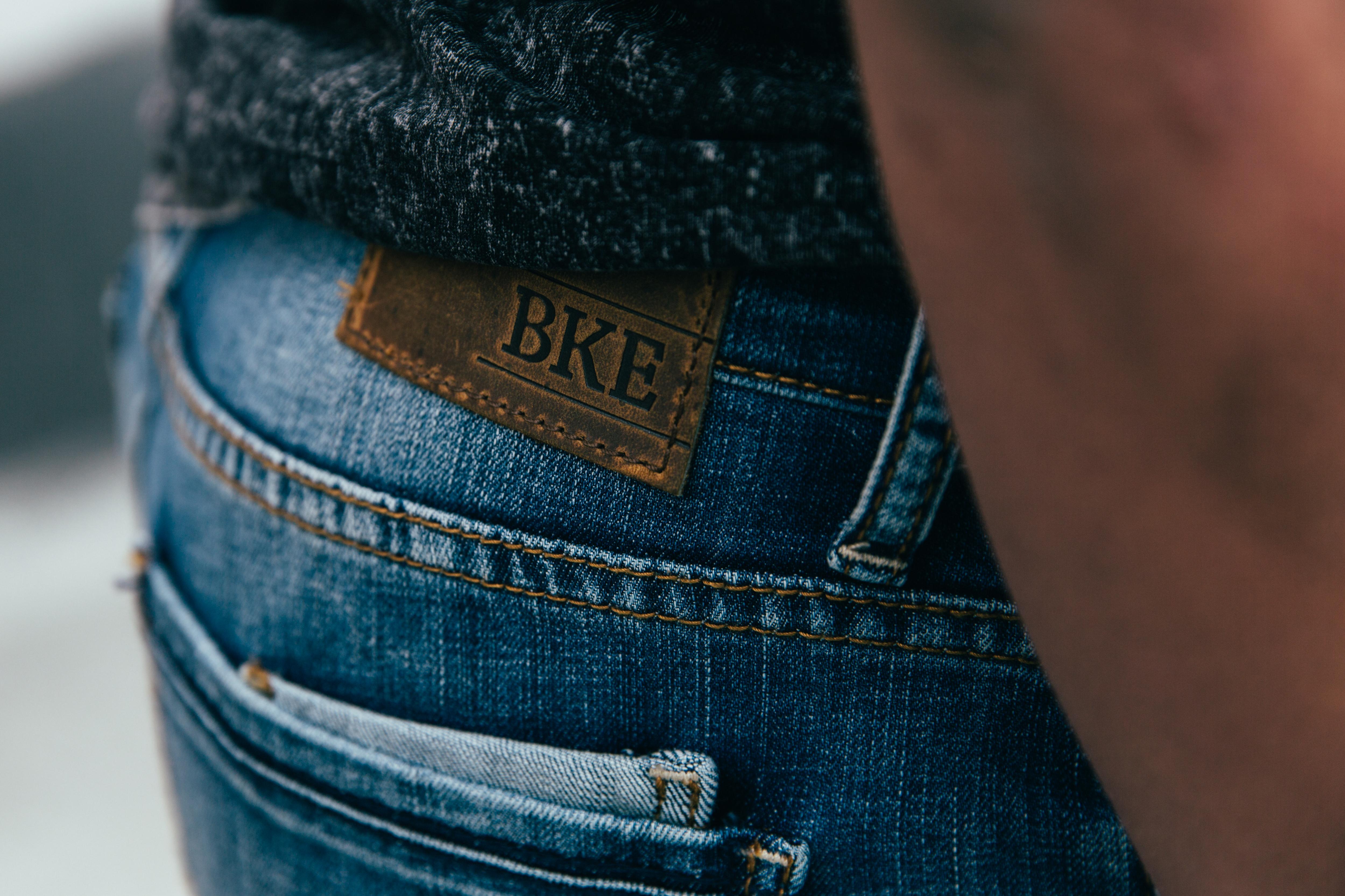 man in pair of medium wash BKE jeans featuring back pocket detailing & cellphone pocket.
