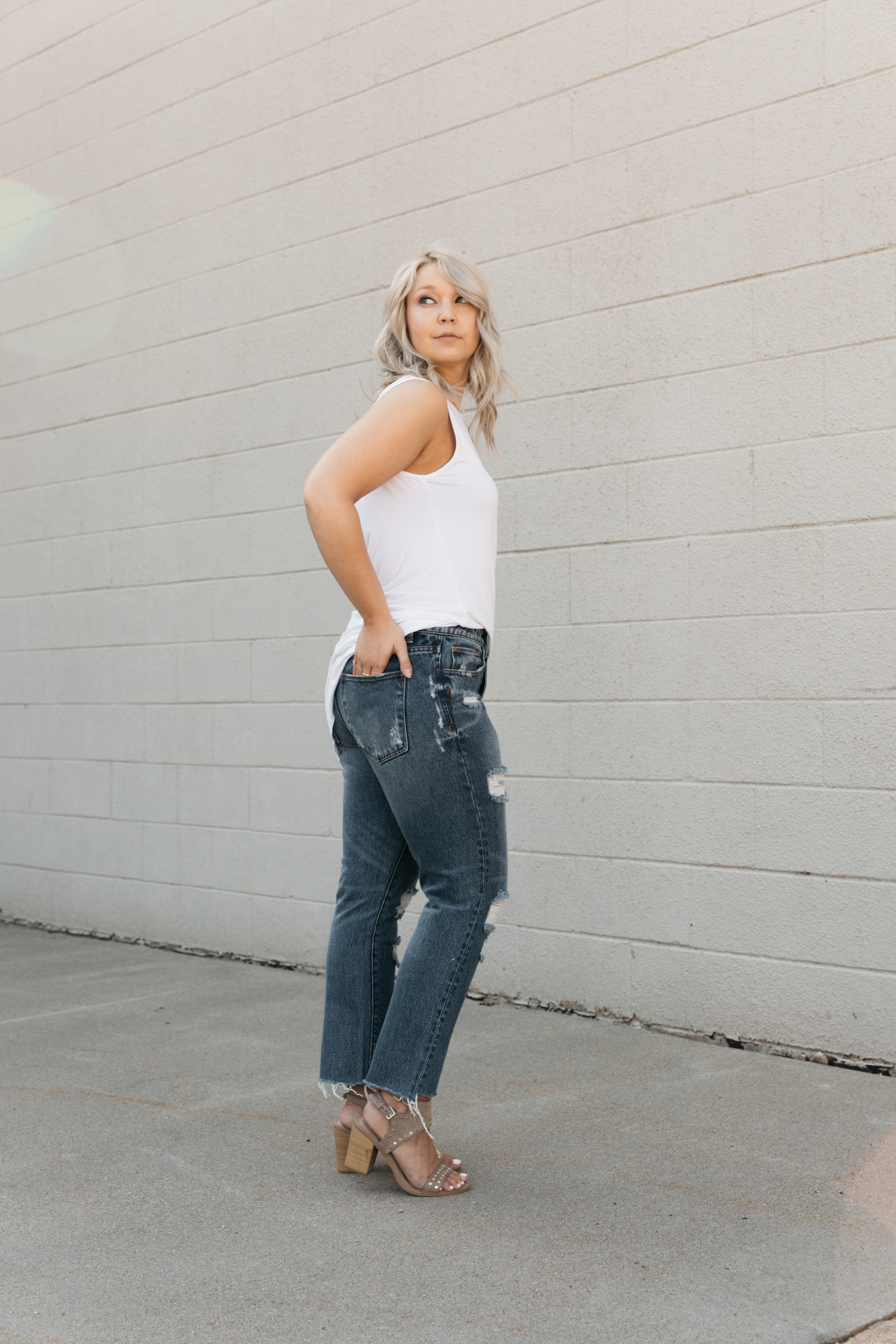 Blonde girl in Gilded Intent straight jeans with a step hem and heels.