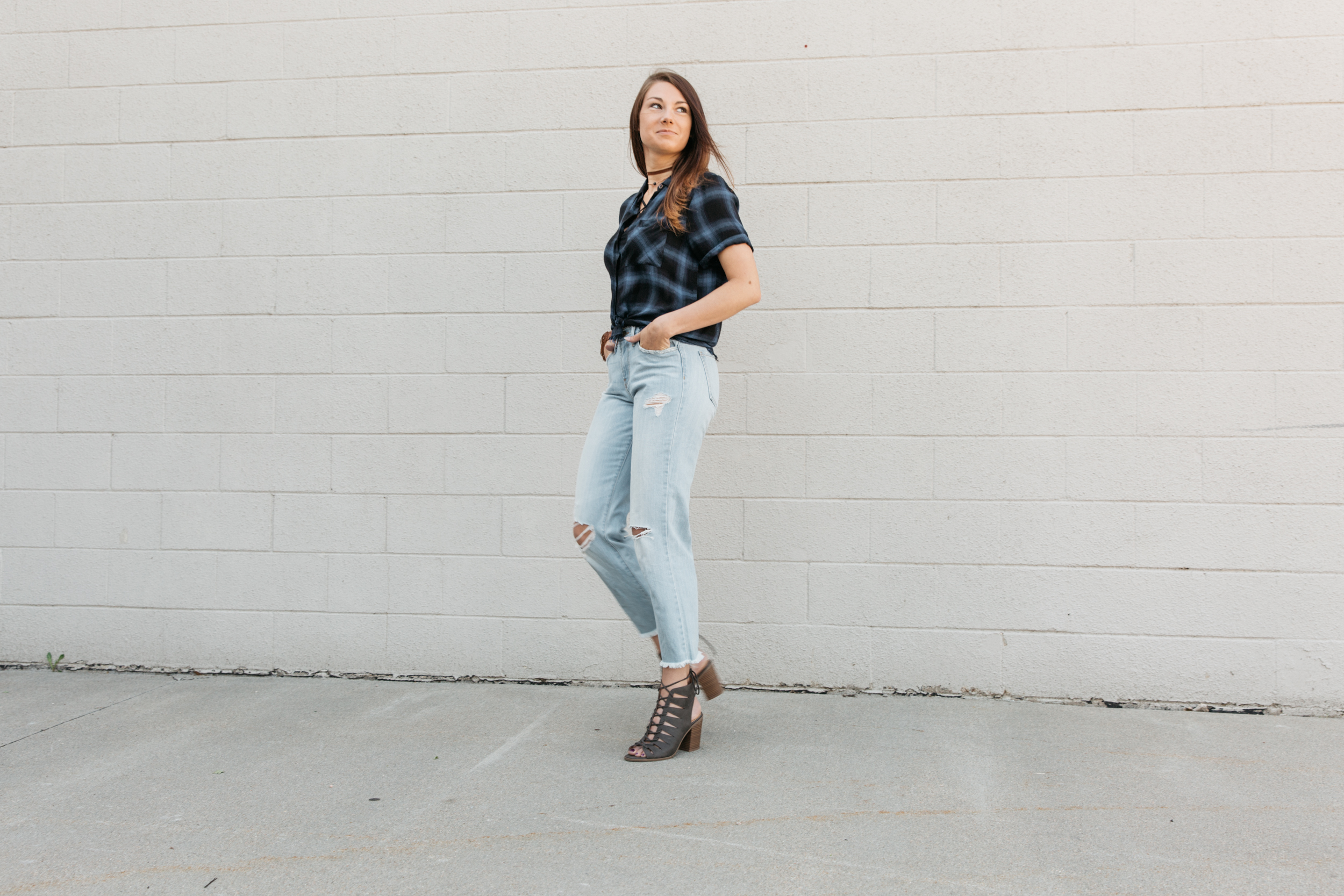Dark haired girl in a Gilded Intent plaid shirt and Flying Monkey straight jeans smiling.