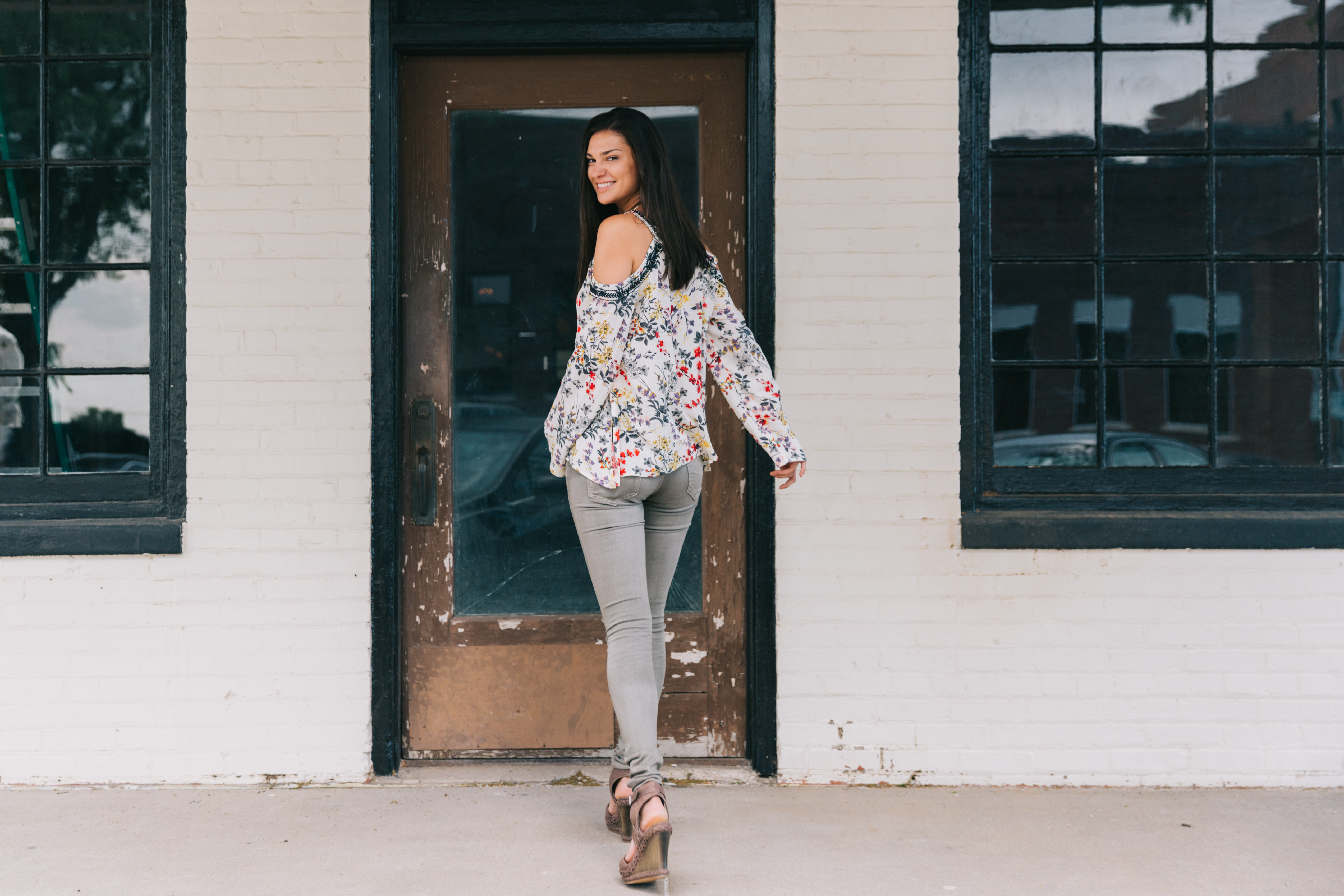 brunette woman walking away from camera, looking over her shoulder smiling. Wearing grey skinny jeans, wedges, and white and blue cold shoulder top.