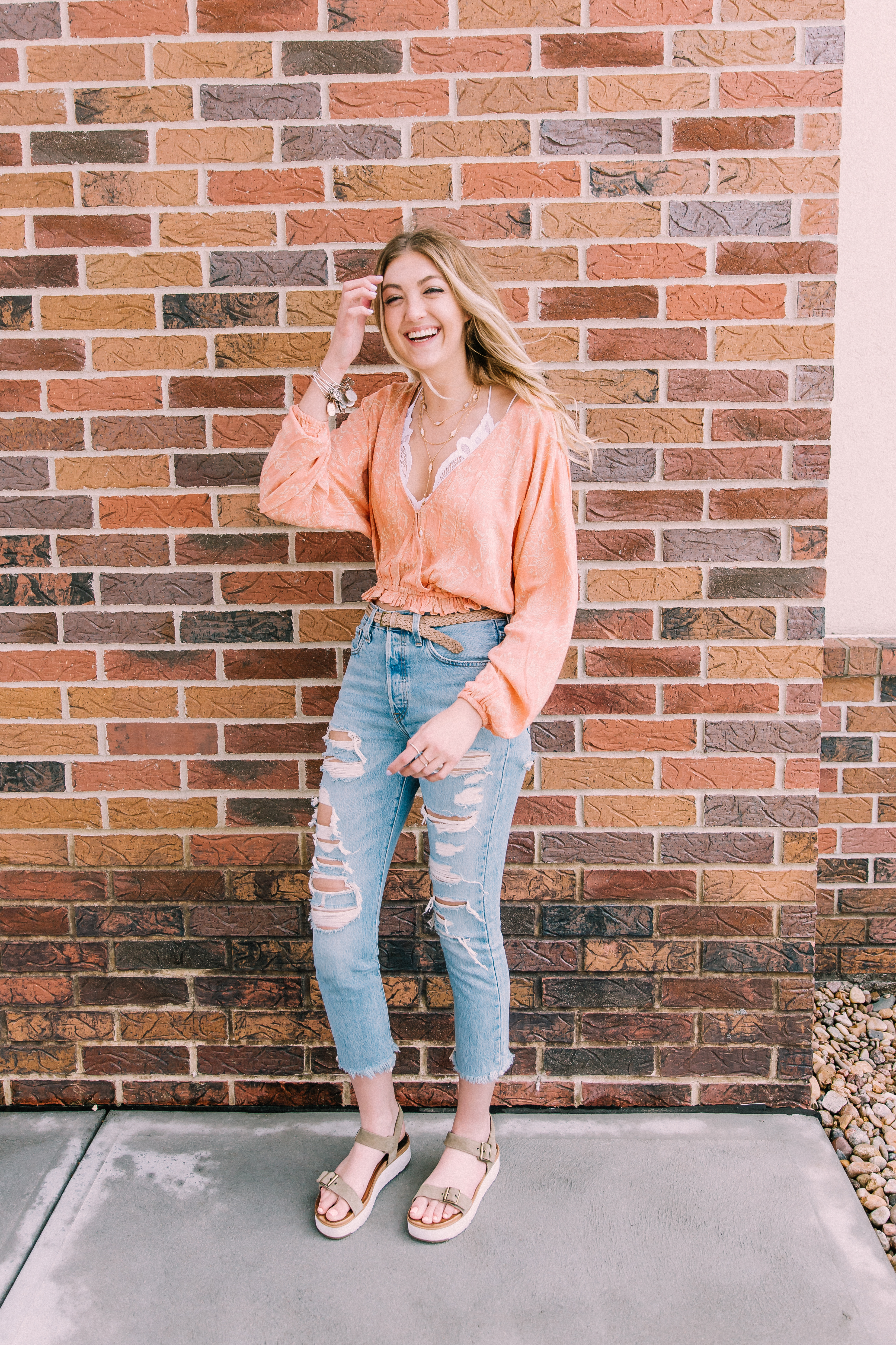 Woman wearing an Amuse Society coral fashion top with a white lace Free People bralette, beige braided belt, destroyed light wash Levi's 501 cropped skinny jeans, and taupe platform sandals from Ugg.