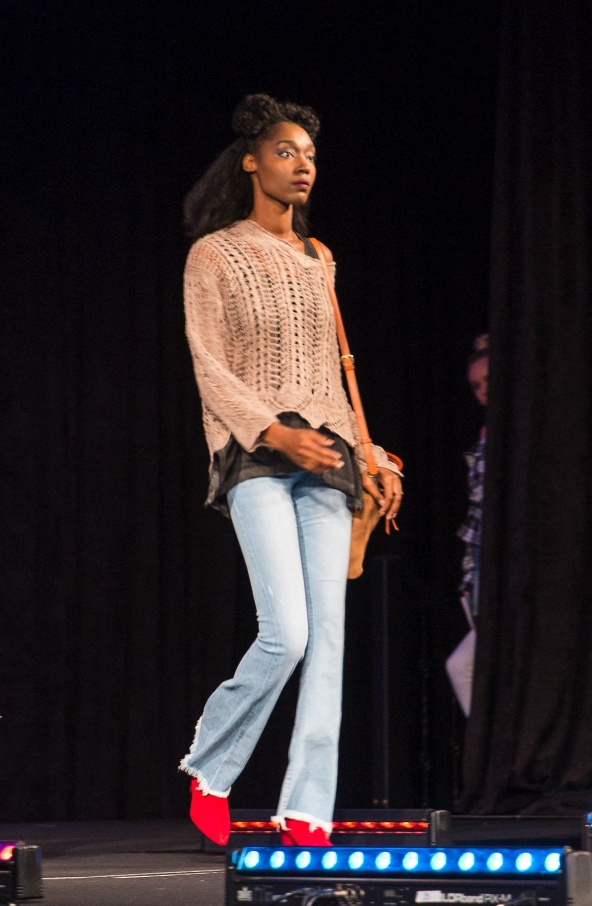 Woman modeling the latest fall trends with Flying Monkey flare denim and hot red booties on the runway.