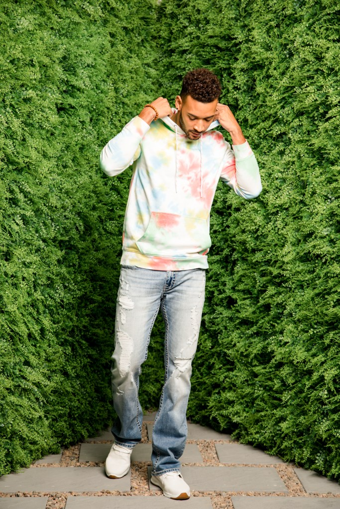 Men's tie-dye hoodies with distressed denim and white sneakers.